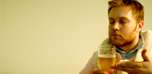 A man smelling a glass of beer