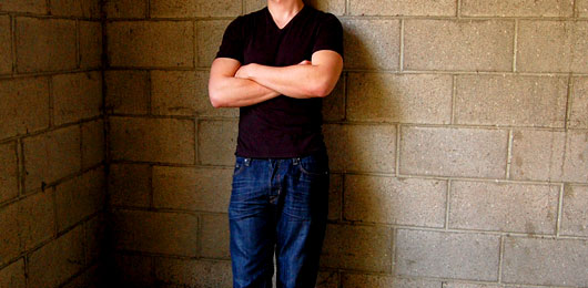 A man standing in front of a brick wall wearing a vneck