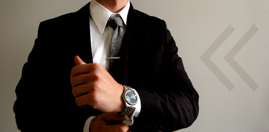 A man wearing a suit and tie holding his watch