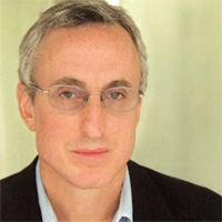 Gary Taubes wearing a suit and tie smiling at the camera