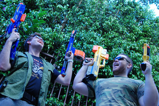 A group of people playing with nerf guns