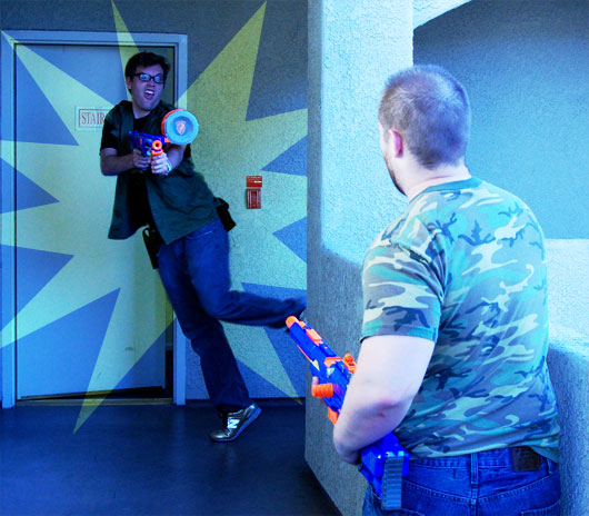 Two men playing with nerf guns