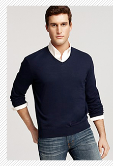 A person standing posing for the camera in a v neck sweater