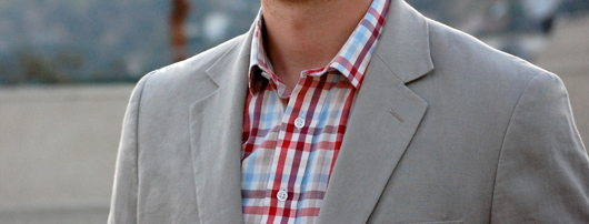 A man wearing a suit and checked shirt