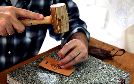 Man using a mallet on a leather wallet