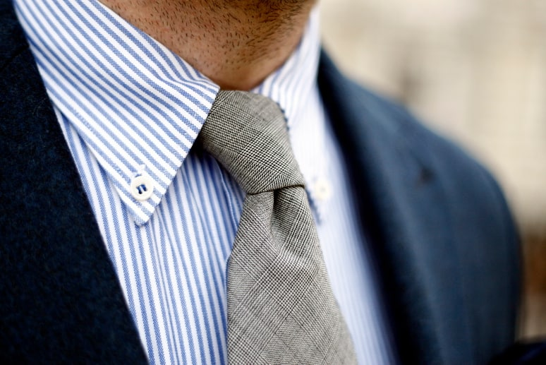 A close up of a man wearing a blue dress shirt and tie