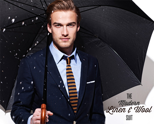 A man wearing a suit and tie holding a umbrella