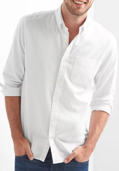A person posing for the camera in a white shirt