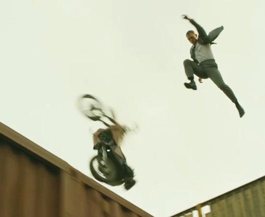 Daniel Craig jumping off motorcycle