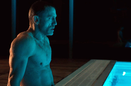 Daniel Craig sitting next to pool