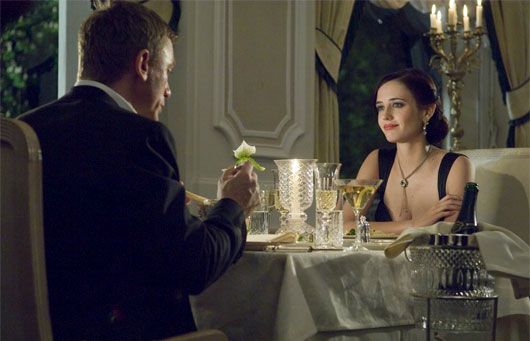 Eva Green sitting at a table with wine glasses, in Casino Royale with Daniel Craig