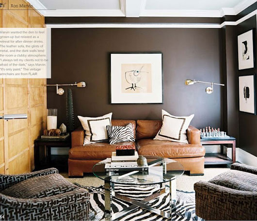 A living room with a couch and a brown wall