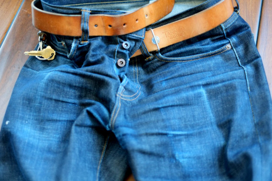 A pair of worn selvedge denim jeans with belt