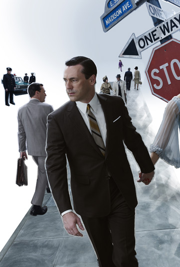 Jon Hamm wearing a suit and tie standing next to a sign