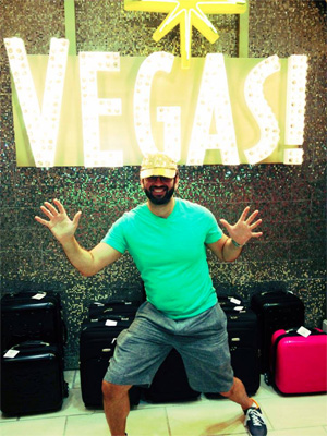 Man standing in front of Vegas sign