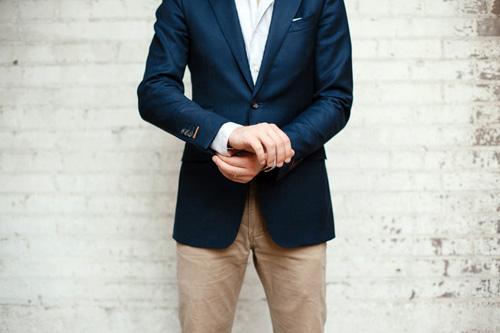 Man wearing nvy blazer and tan pants