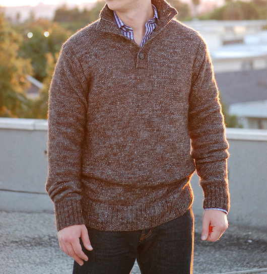 A man standing in front of a building in a sweater