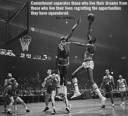 A group of people playing on a basketball court with a Bill Russell quote