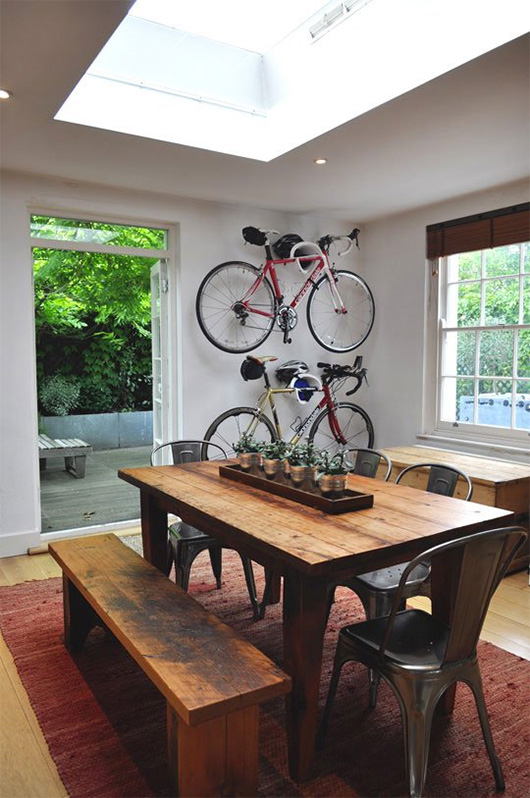 A dining room table in front of a window with bicycles