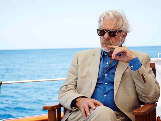 Giancarlo Giannini wearing sunglasses and sitting in front of a body of water, with Johnnie Walker and Actor