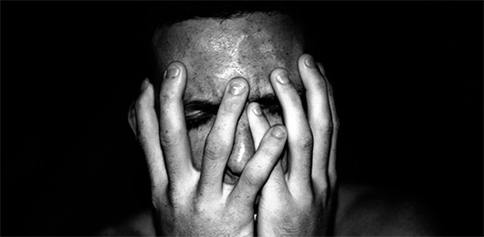 Man holding his face in his hands