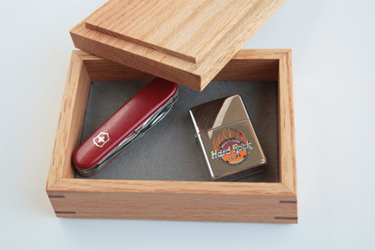 A wooden box with knife and lighter