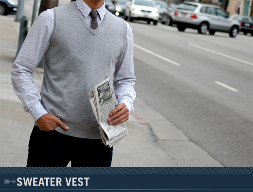 A man standing wearing a sweater vest