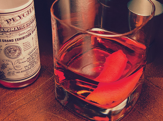 A sazerac cocktail in front of ingredients