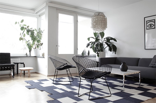 A living room filled with furniture and a large window with geometric rug