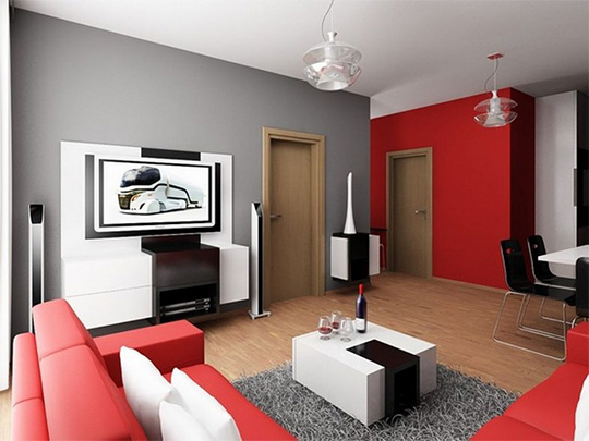 A living room filled with furniture with a red wall