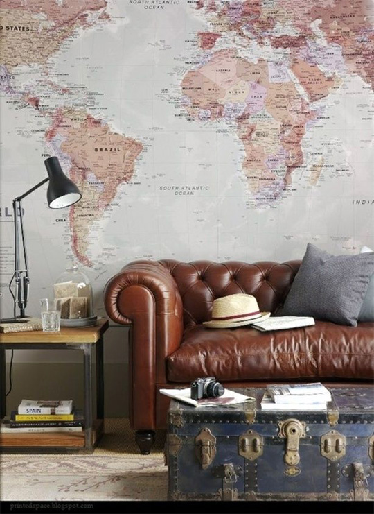 Brown leather couch with giant map on wall