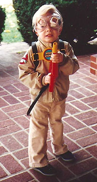 A small boy dressed in a Ghostbusters costume