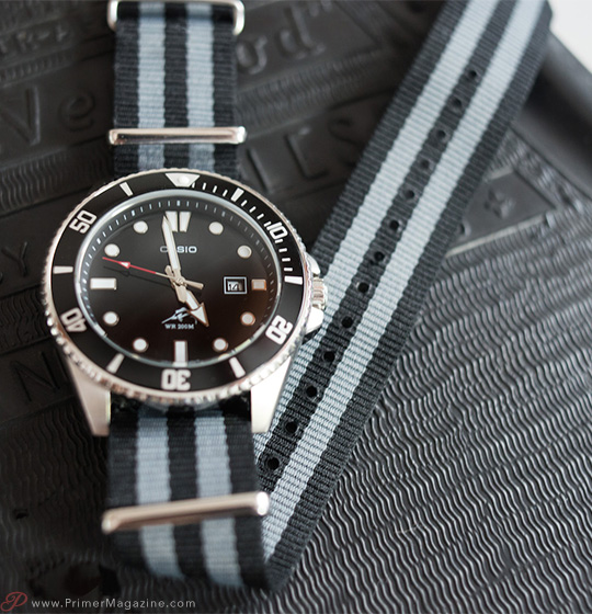 A close up of a watch on a striped strap