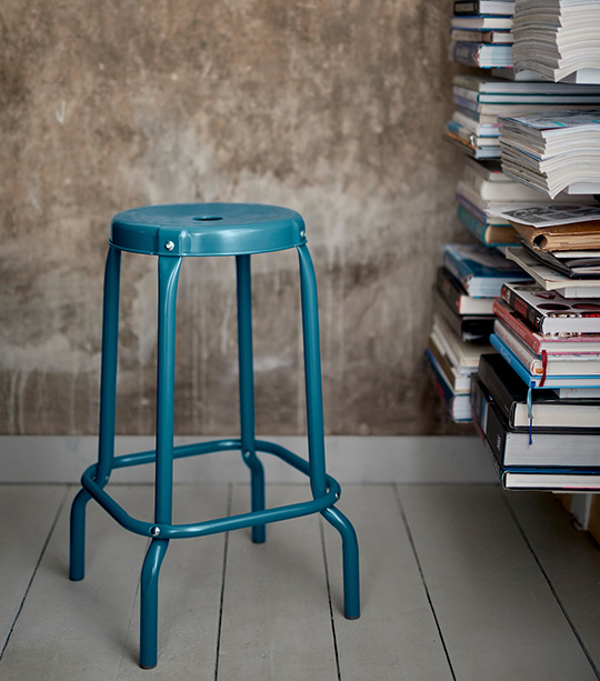 A stool sitting in front of a shelf