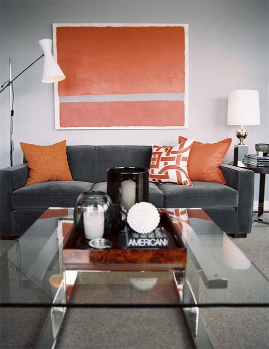 A living room filled with furniture and orange artwork