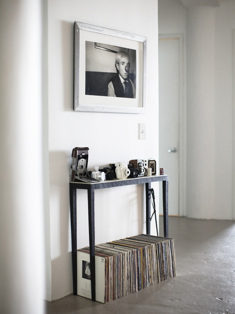 A record shelf with a photo of Andy Warhol