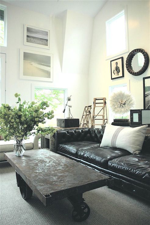 A living room filled with black leather couch and a large window