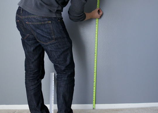 Using a tape measure to mark wall