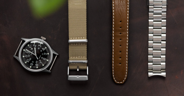a watch with three different types of watch bands, canvas, leather, and metal