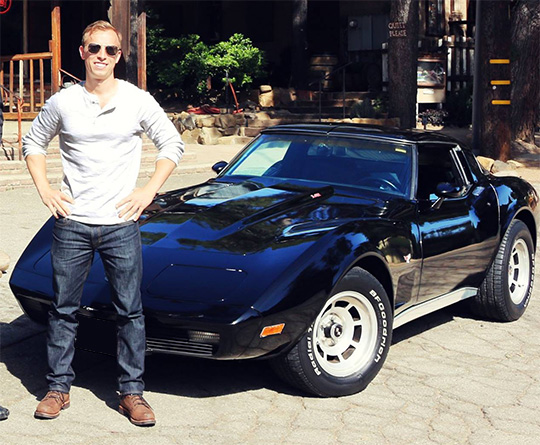 A man standing in front of a c3 corvette