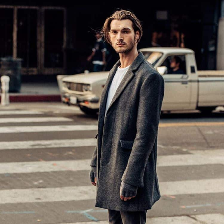 A person wearing a long coat on the street