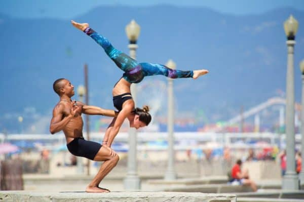 Fit couple practices acro yoga on the beach