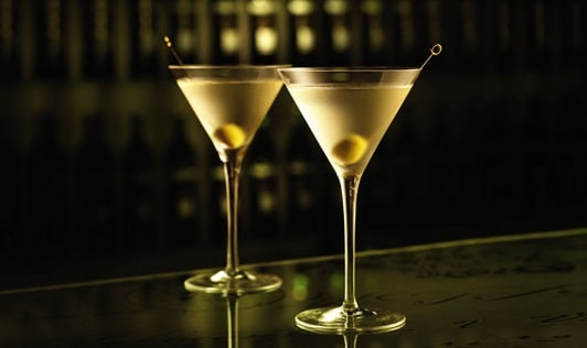 Two gin martinis side-by-side on a bar