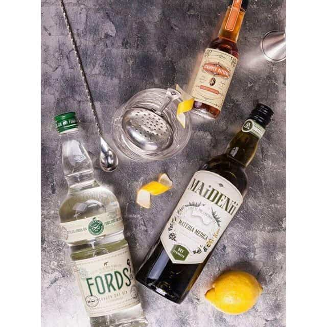 The ingredients of a traditional martini: Gin, vermouth, and orange bitters with lemon peel