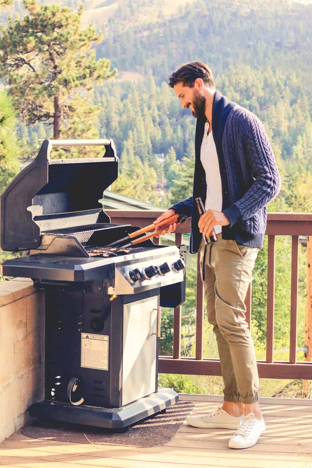 A man standing in front of a grill wearing khaki pants