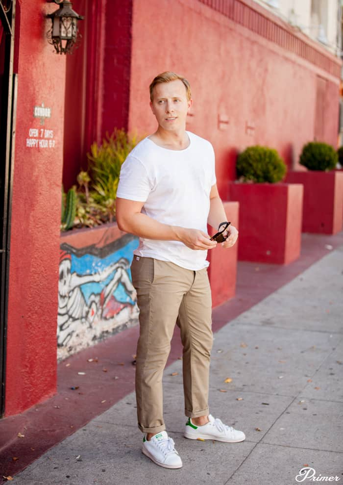 A man standing on a sidewalk with a white tshirt and khaki pants