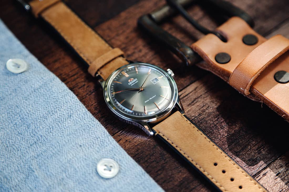 A watch sitting on top of a wooden table