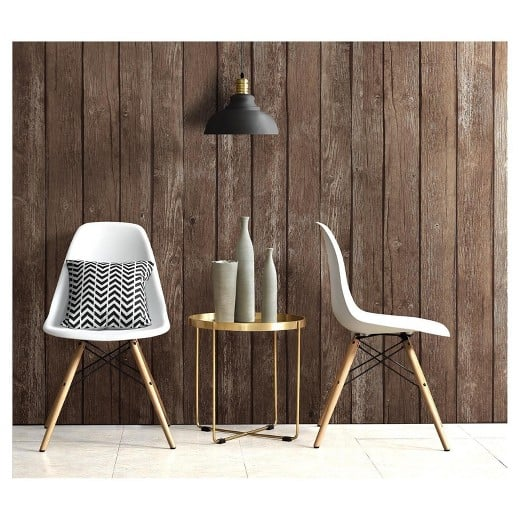A chair sitting in front of a wooden wall