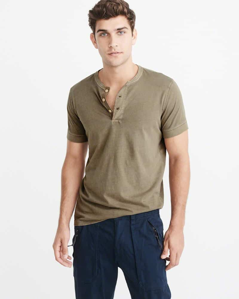 A person standing posing for the camera in a green henley