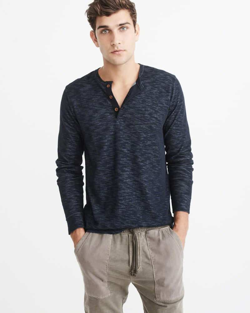 A person standing posing for the camera in a blue henley